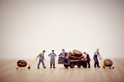Miniature workers loading coffee beans on truck.